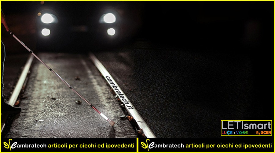 image of the LETIsmart Luce, in operation, then lit, applied to a white cane HG4690 used at night in the city by a person who is crossing a road while a car comes with obviously the headlights on.